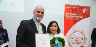 Đại diện INEC (trái) nhận chứng nhận từ Đại học JCU Singapore